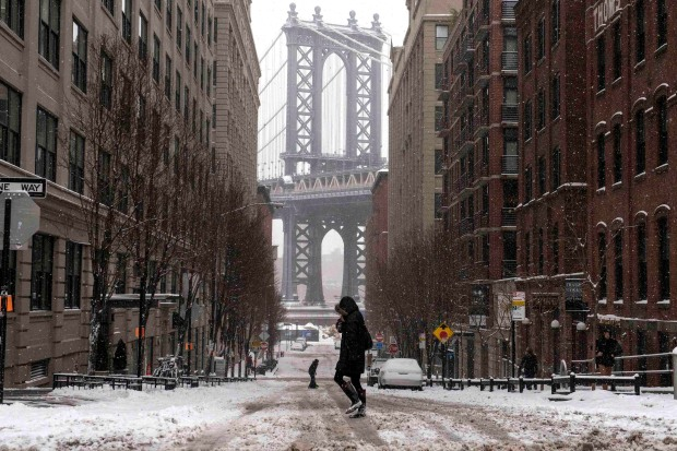 The Manhattan Bridge is seen in the background as commuters make their way through the streets of Dumbo after a snow storm in New York